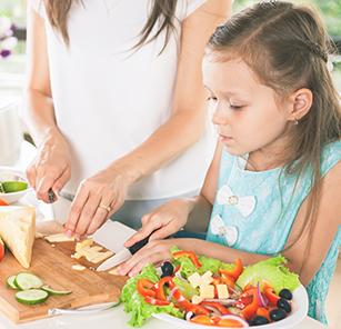 Girl helping Mom cut vegetables